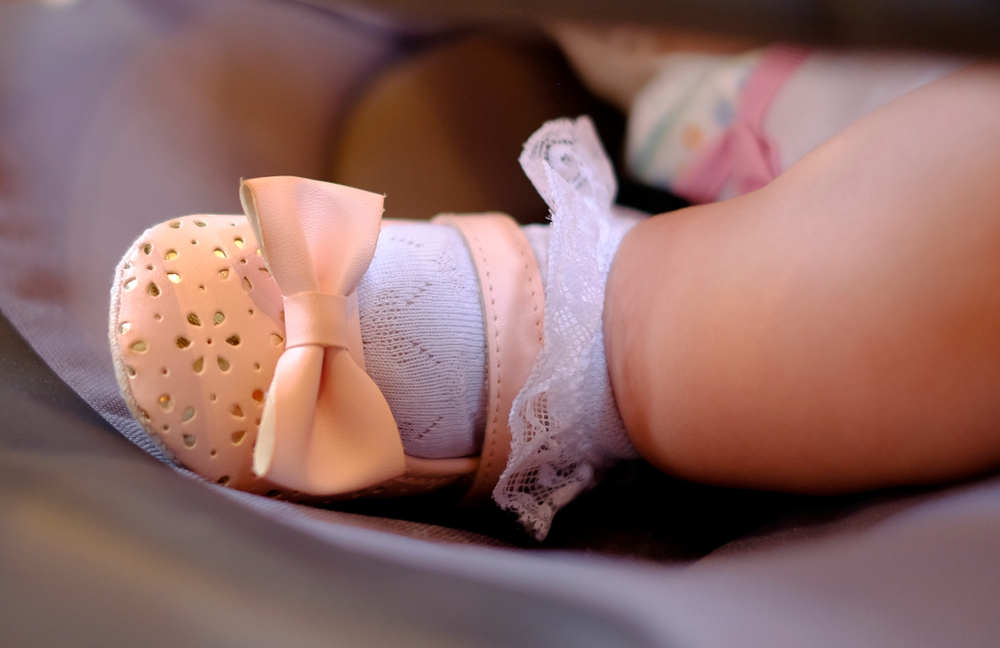 close up on baby's frilly sock and pink shoe